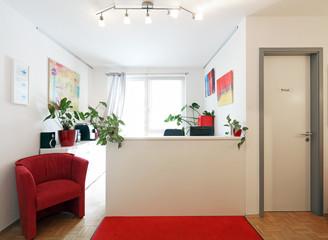 Empfangstresen mit Wartesessel und Tür