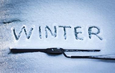 Winter written in snow on car windscreen below windscreen wiper