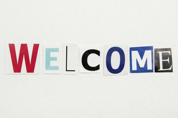 word welcome cut from newspaper on white handmade paper