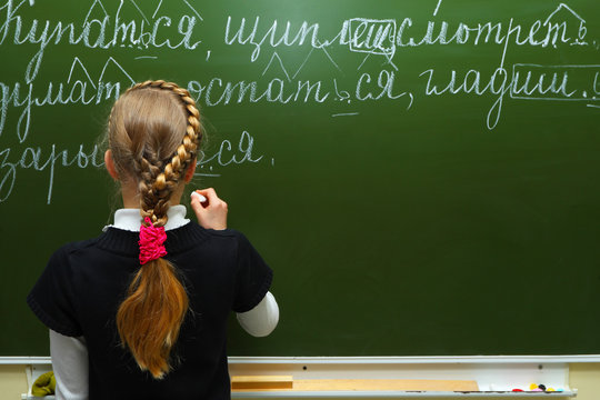 The schoolgirl writes chalk on a blackboard
