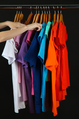 Variety of casual shirts on wooden hangers, isolated on black