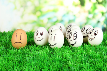 Eggs with funny faces on grass on bright background