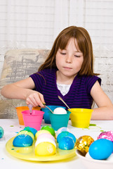 Young girl coloring Easter Eggs - egg halfway into cup of dye