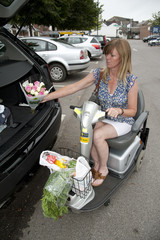 Disabled shopper loading car with shopping