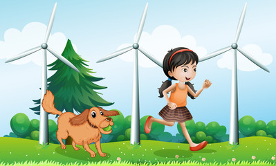Poster de jardin Chiens A girl playing with her dog near the windmills