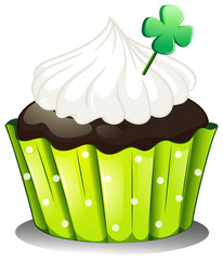 A chocolate cupcake with a green plant
