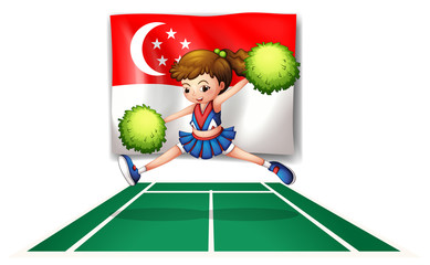 A cheerleader with green pompoms and the flag of Singapore
