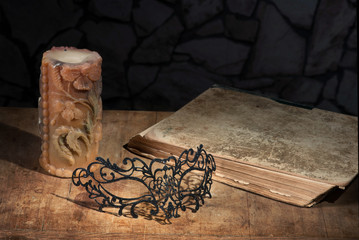 Vintage still life with lacy mask, ancient book and candle