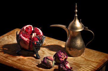 Vintage still life - pomegranate, dried roses and arabic teapot
