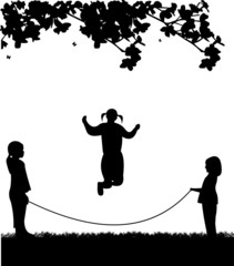 A little girls playing skipping rope in park in spring