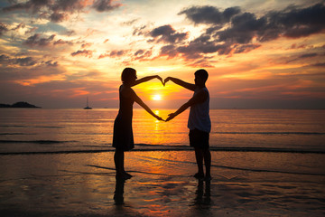 Couple holding hands heart-shaped on the sea beach