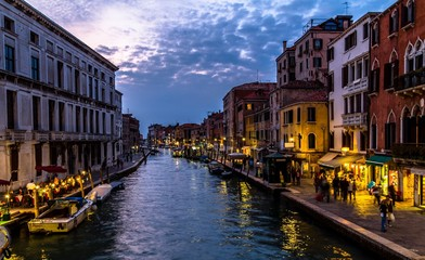 Venice channel at nightfall, with people (unrecognizable)