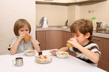 Two boys eat in kitchen