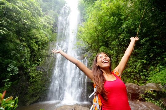 Hawaii woman tourist excited by waterfall