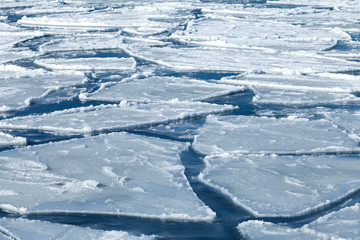 Winter background, blocks of ice on frozen blue Sea