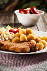 Breaded chop, prepared potatoes and salad. Mysterious light.