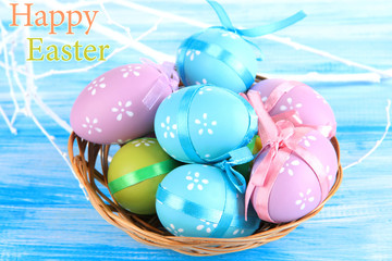 Easter eggs in basket, on blue wooden background