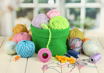 Colorful yarn for knitting in green basket