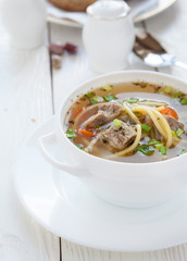 meat soup with vermicelli in a white tureen