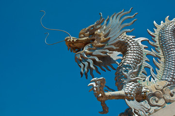 Half-length silver dragon statue on blue sky