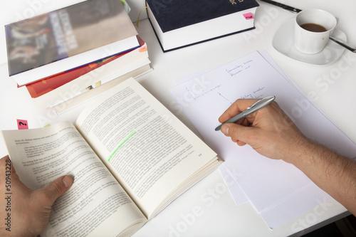Student lernt, macht Notizen, auf einem Schreibtisch mit Büchern