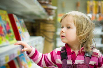Adorable girl in shopping cart select books on shelves in superm