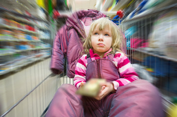 Adorable girl with jacket sit in shoping cart with bar of chocol