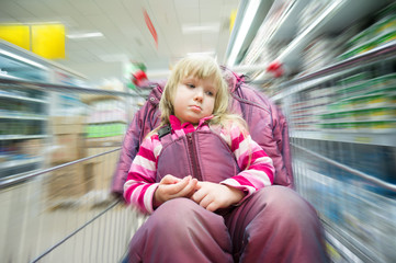 Adorable girl sit in shoping cart in milk products department in