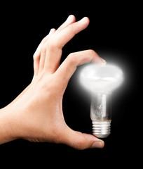 Hand holding a light bulb, isolated dark