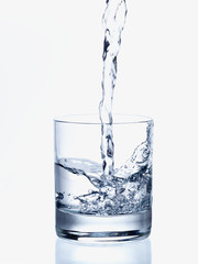 Pouring fresh water in a transparent glass, on white background