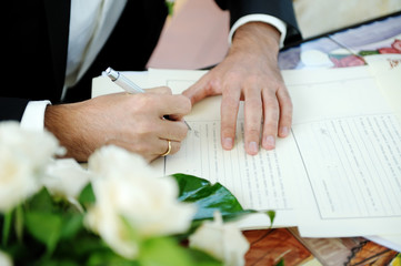 Groom signing wedding contract