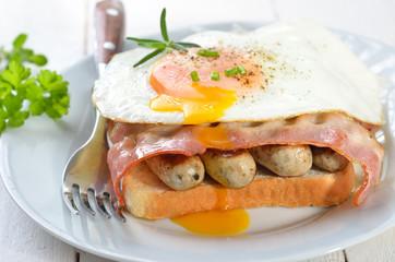 Deftiger Frühstückstoast mit Spiegelei, Würstl und Speck