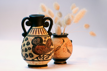 two greek vases with dried grass