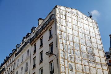 Immeuble avec façade bâchée.