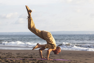 Wall Mural - Strong man exercising yoga upside down on coastline