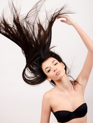 Young attractive brunette woman with long hair in the air.