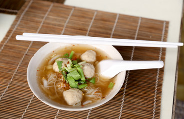 Meat balls noodle in a white bowl with chopsticks