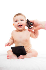 cheerful baby plays with  tablet PC and mobile phone