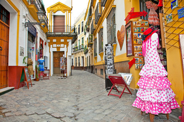 Shopping street with typical flamenco dress in Seville, Spain.