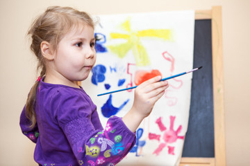 Thoughtful small Caucasian child holding painting brush in hand