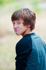 Young teen looking at camera with frown face