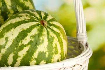 Ripe watermelon in wicker basket on green background close-up