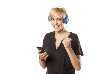 happy girl plays with headphones and music from her phone