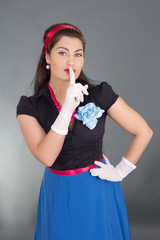 woman in retro clothes with finger on lips