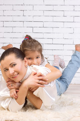 Portrait of daughter riding on her mother hugging