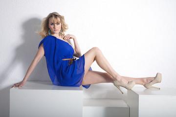 Junge hübsche Frau sitzt sexy auf Würfel im Studio