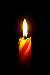 Burning red candle on a black background