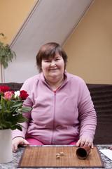 Behinderte Frau würfelt und hat Spass