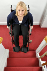 Junge Frau mit Rollstuhl vor Treppe
