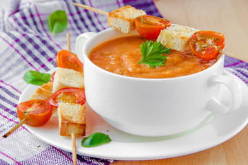 Warm tomato soup on dinner with crouton cherry tomatoes on stick